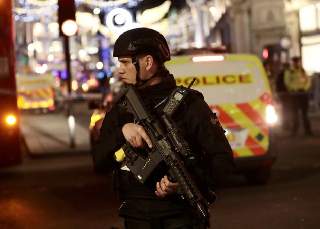 An armed officer standing guard near a cordon during the