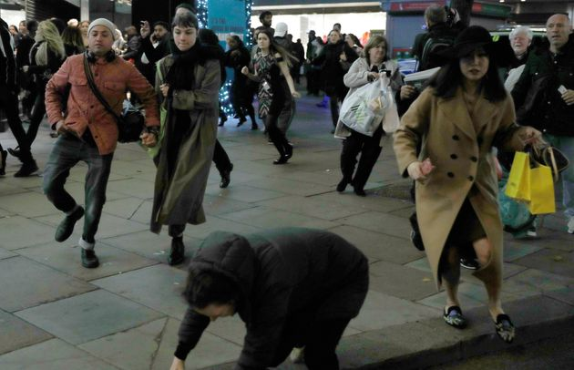 A woman stumbles as people run down Oxford Street on Friday