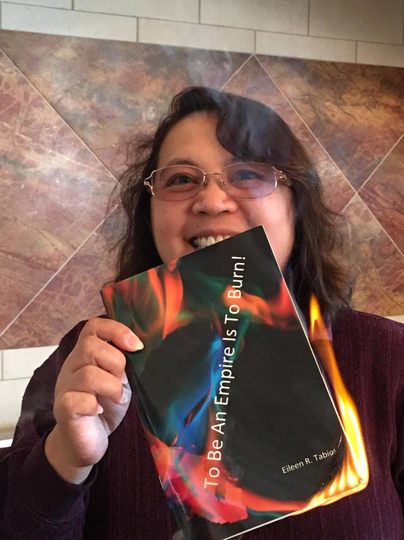 Poet Eileen Tabios with her poetry chapbook 'To Be An Empire Is To Burn!' — which she set on fire to reflect its title.  <a r
