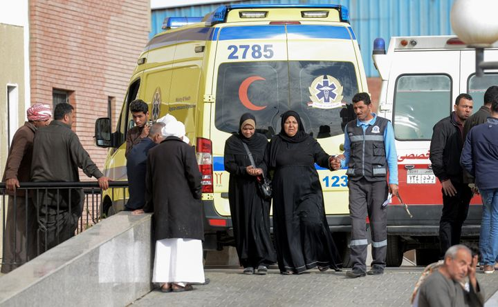 Relatives of the victims of the bomb and gun assault on the North Sinai Rawda mosque walk past an ambulance while waiting out