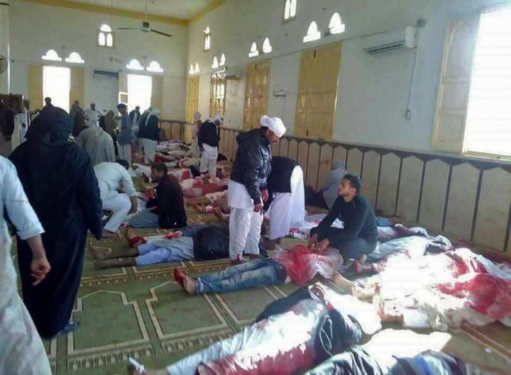 Egyptians walk past bodies following a gun and bombing attack at the Rawda mosque, roughly 40 kilometers west of the North Si