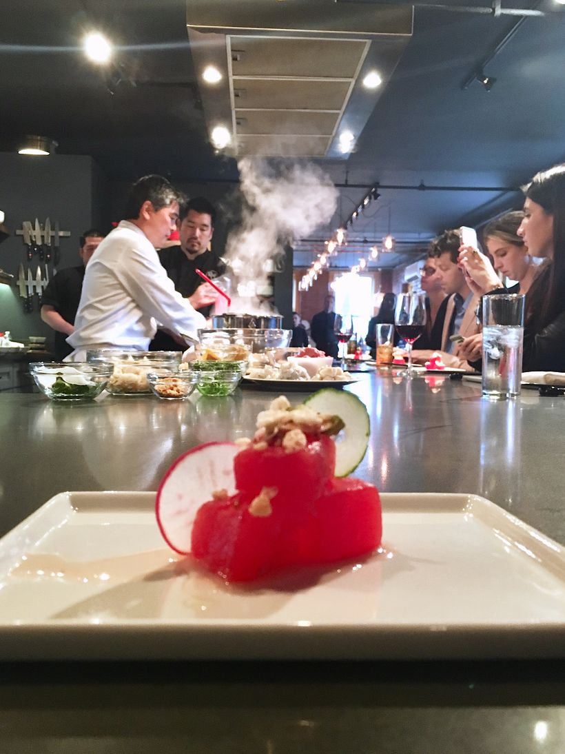 In the foreground: watermelon poke; in the background: Chef Yamaguchi prepares meals for guests