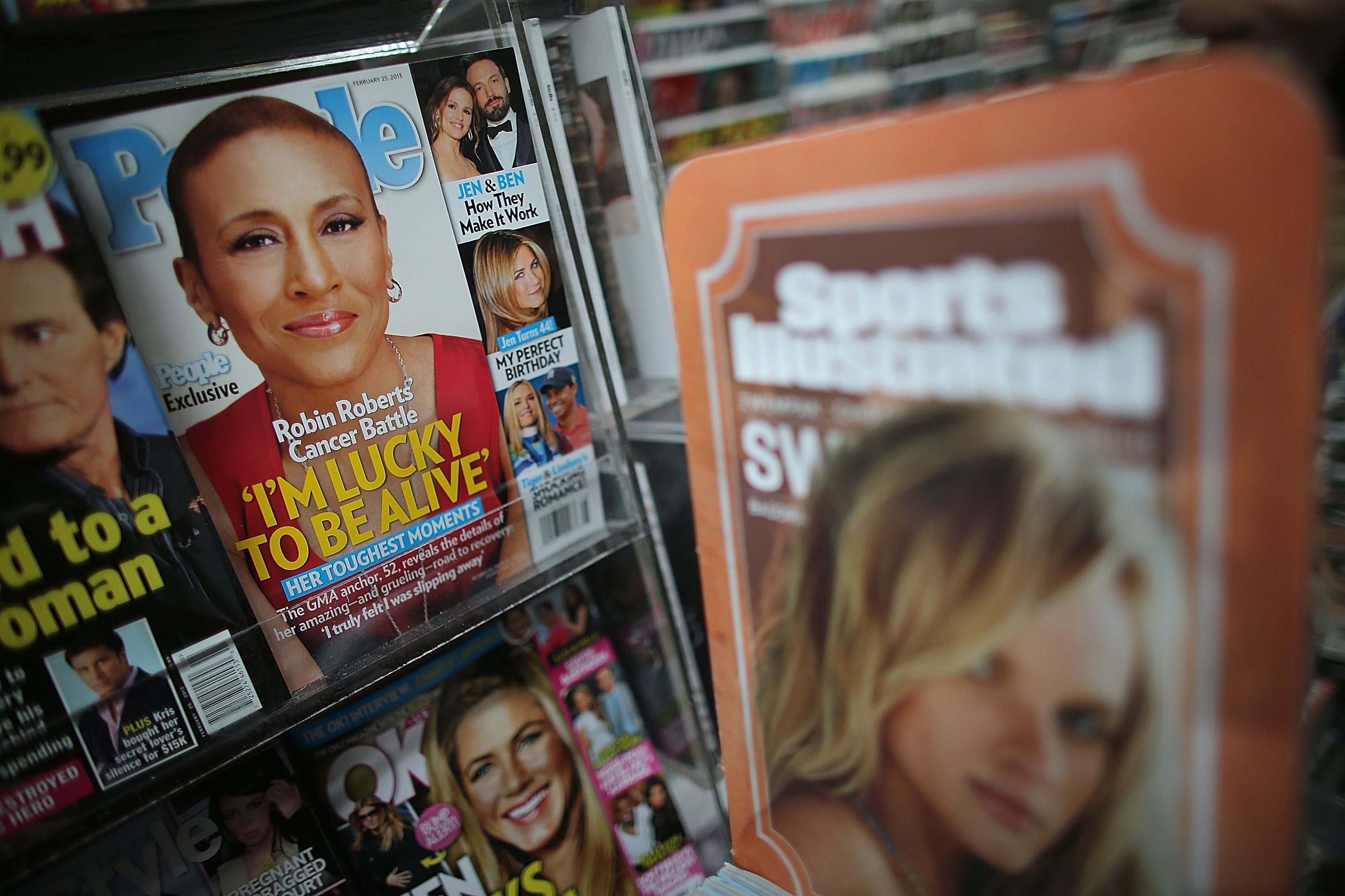 NEW YORK, NY - FEBRUARY 13:  Issues of People magazine (L) are displayed next to a Sports Illlustrated advertisement at a newsstand in Manhattan on February 13, 2013 in New York City. Time Warner Inc. is reportedly in talks to sell most of its magazine group, including People, InStyle and Entertainment Weekly, to the Meredith Corporation. Time Warner would reportedly retain control of flagship titles Time, Sports Illustrated and Fortune.  (Photo by Mario Tama/Getty Images)