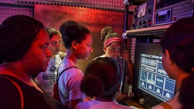 Participants in GenCyber, a cybersecurity summer camp for middle-school girls, work to solve a mystery at the Spy Museum in W