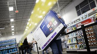 A shopper carries an Insignia Roku TV television at a Best Buy Co. store in Louisville, Kentucky, U.S., on Thursday, Nov. 23, 2017. The highly competitive retail environment doesn't appear to be letting up for the holiday season, as companies aggressively vie for consumers' dollars by offering Black Friday promotions BEFORE Black Friday. Photographer: Luke Sharrett/Bloomberg via Getty Images