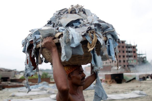 A worker balances a basket of waste products to be processed at a tannery at Hazaribagh in