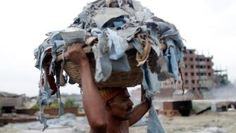A worker balances a basket of waste products to be processed at a tannery at Hazaribagh in Dhaka June 28, 2011. REUTERS/Andrew Biraj (BANGLADESH - Tags: ENVIRONMENT EMPLOYMENT BUSINESS)