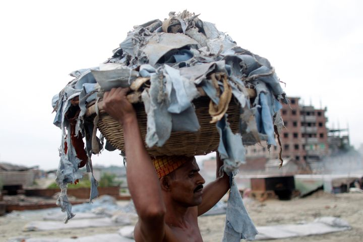 A worker balances a basket of waste products to be processed at a tannery at Hazaribagh in Dhaka, Bangladesh.
