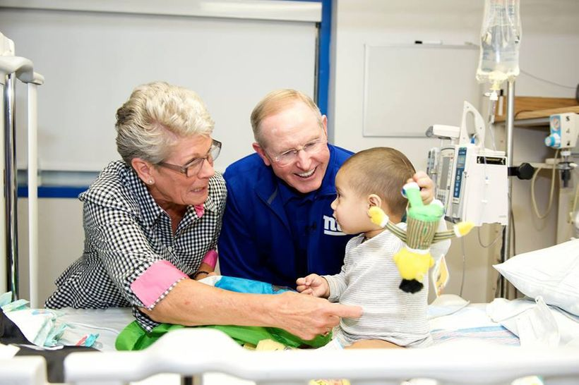 Tom and Judy Coughlin visit with a pediatric cancer patient.