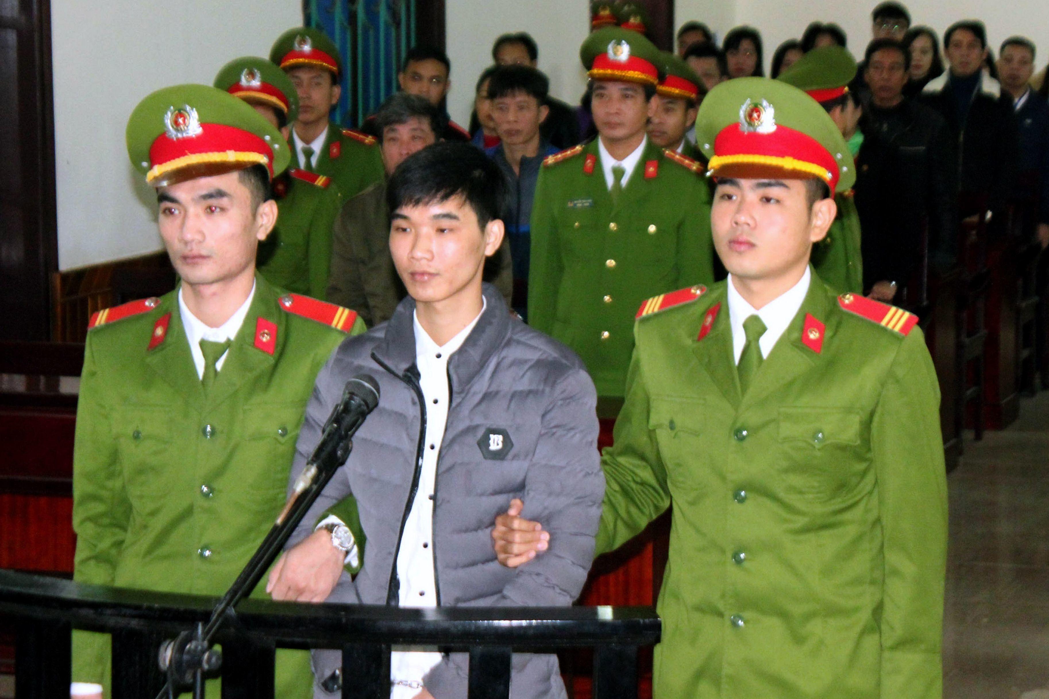 This photo from the Vietnam News Agency taken on November 27, 2017 shows activist Nguyen Van Hoa (C) standing trial at a local people's court in the central province of Ha Tinh. A Vietnamese court on November 27 jailed a blogger for seven years for disseminating anti-state 'propaganda' including articles which supported protests against a Taiwanese firm responsible for a toxic leak. Nguyen Van Hoa, 22, an environmental activist, was accused of instigating protests against authorities via his Facebook account, mainly following the 2016 toxic leak at a steel factory operated by Taiwan's Formosa. / AFP PHOTO / Vietnam News Agency / Vietnam News Agency        (Photo credit should read VIETNAM NEWS AGENCY/AFP/Getty Images)