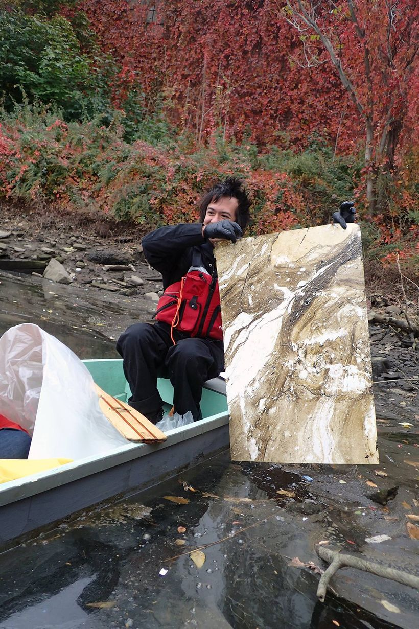 Sto pulling a pollution suminagashi print from a polluted waterway.