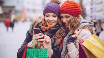 Female friends shopping in city. Holding shopping bags and using smart phone. Wearing warm clothes, hat and scarf. Vienna, Austria. Day time.