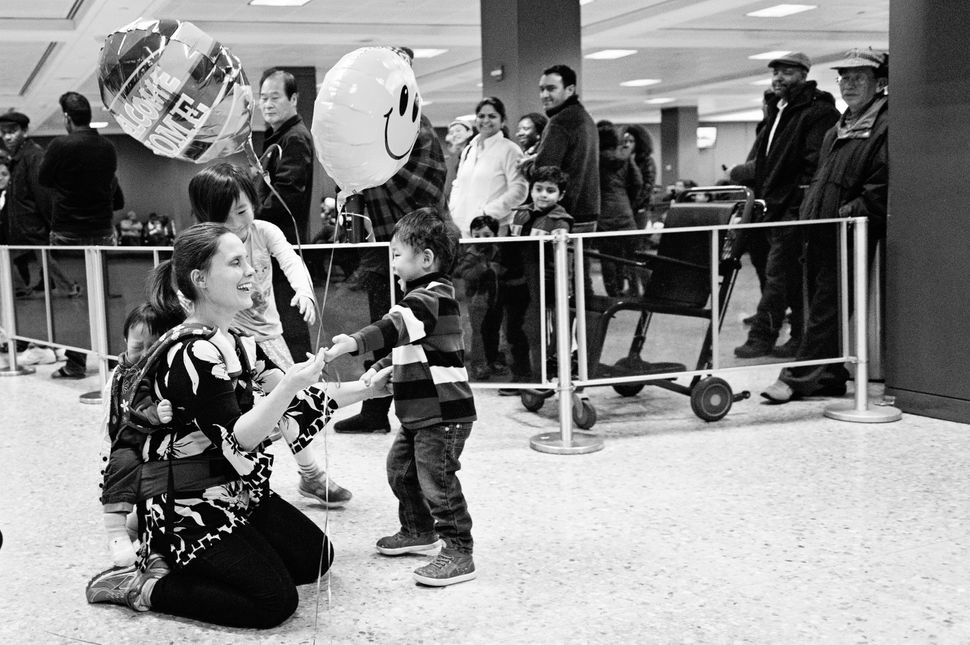 """""""Emily is greeted at the airport by her two older sons after bringing home Noa from South Korea."""" -- Sandra Eminger"""