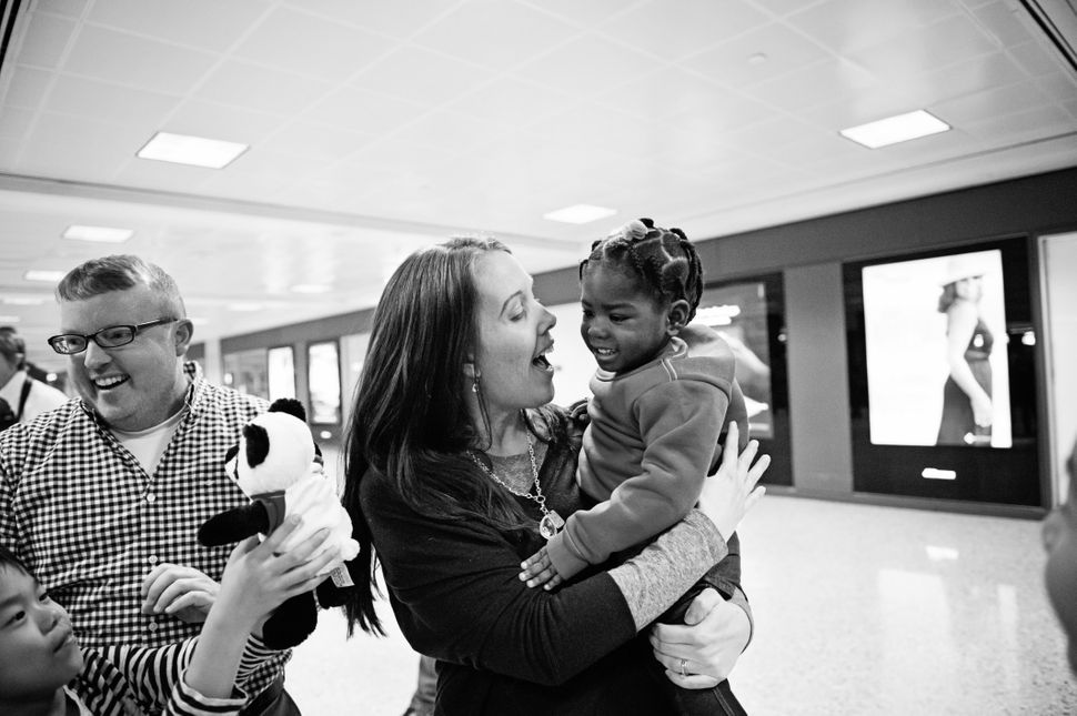 """""""Olivia, adopted from Congo, meets her family."""" -- Sandra Eminger"""