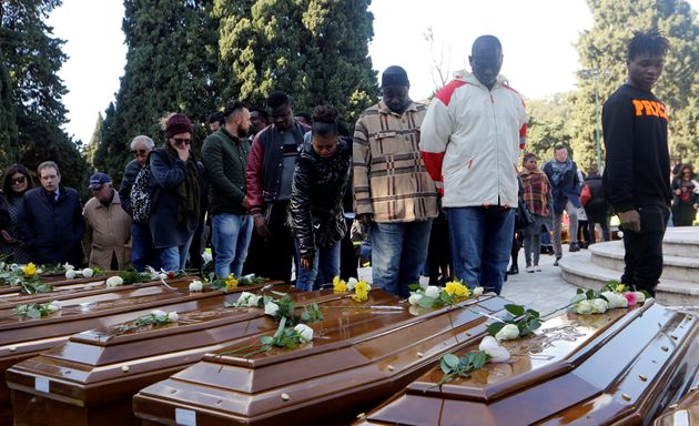 In this Nov. 17 photo, people in Italy's Salerno cemetery pay respect to 26 Nigerian women who died while...