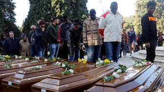 People pay respect as they walk by the coffins ahead of the funeral service for 26 Nigerian women who died last week while crossing the Mediterranean Sea, at the Salerno cemetery, Italy, November 17, 2017. REUTERS/Ciro De Luca