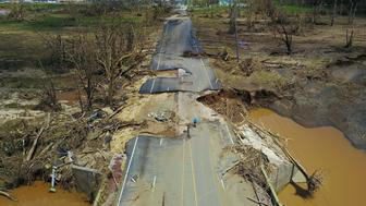 TOPSHOT - A man rides his bicycle through a damaged road in Toa Alta, west of San Juan, Puerto Rico, on September 24, 2017 following the passage of Hurricane Maria. Authorities in Puerto Rico rushed on September 23, 2017 to evacuate people living downriver from a dam said to be in danger of collapsing because of flooding from Hurricane Maria. / AFP PHOTO / Ricardo ARDUENGO        (Photo credit should read RICARDO ARDUENGO/AFP/Getty Images)