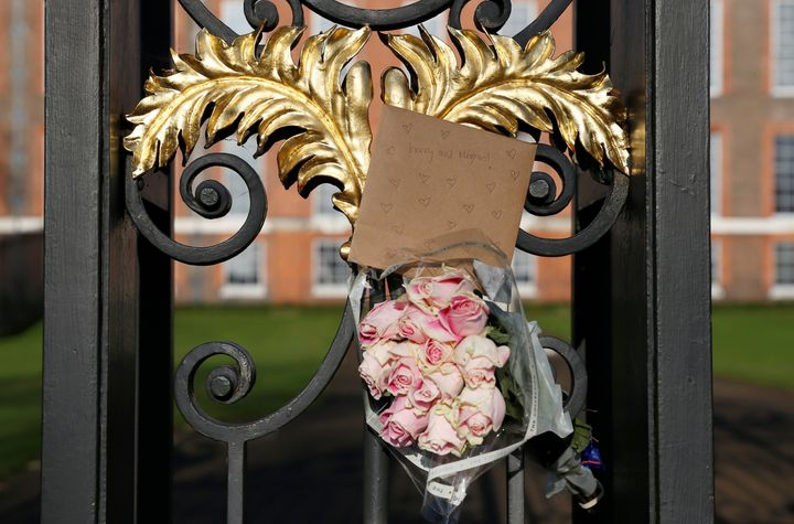 Flowers and a card addressed the Britain's Prince Harry and Meghan Markle are seen attached to the railings of Kensington Palace in London on Nov.28, 2017.