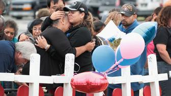 SUTHERLAND SPRINGS, TX - NOVEMBER 10:  Visitors mourn the loss of family and friends at a memorial where 26 crosses were placed to honor the 26 victims killed at the First Baptist Church of Sutherland Springs on November 10, 2017 in Sutherland Springs, Texas. On November 5, a gunman, Devin Patrick Kelley, shot and killed the 26 people and wounded 20 others when he opened fire during Sunday service at the church.  (Photo by Scott Olson/Getty Images)