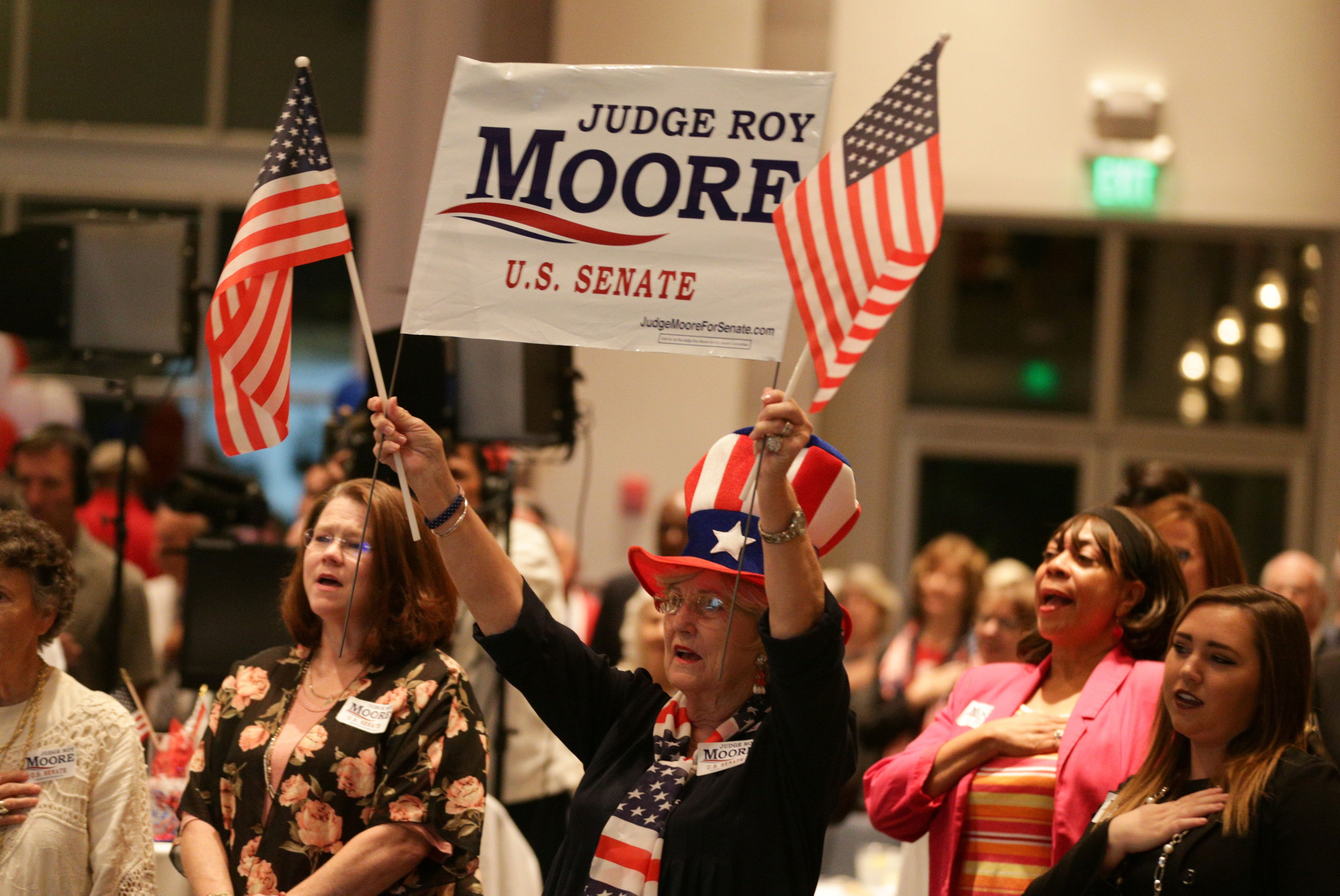 A Republican Roy Moore supporter stands for the national anthem during the runoff election for the Republican nomination for Alabama's U.S. Senate seat vacated by Attorney General Jeff Sessions, at the RSA Activity Center in Montgomery, Alabama, U.S. September 26, 2017.  REUTERS/Marvin Gentry