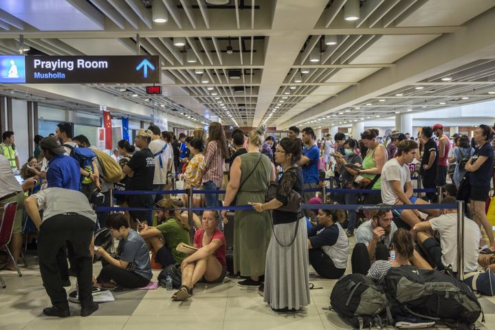 Passengers wait in lineat the ticketing counter at Ngurah Rai International Airport near Denpasar, Bali, on Tuesday. Th