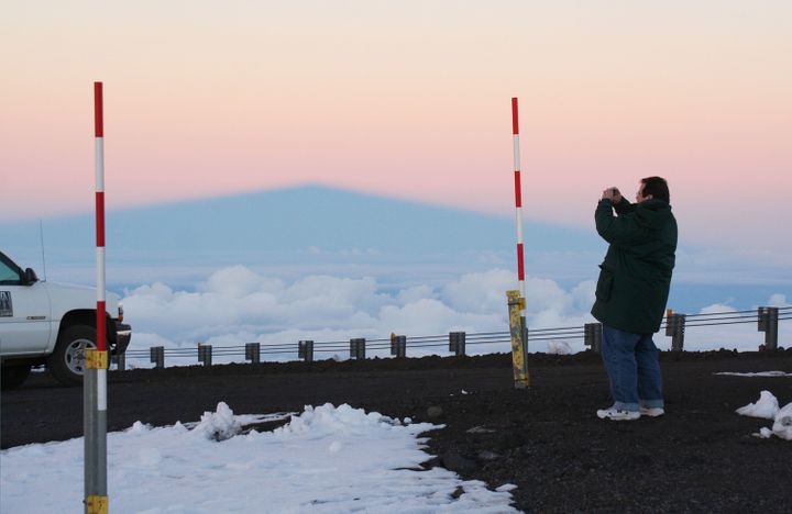 A visitor takes photos of snow on Mauna Kea in this undated photo. The red-and-white poles measure snow depth.