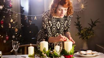 Woman lights candles on Christmas dining table.