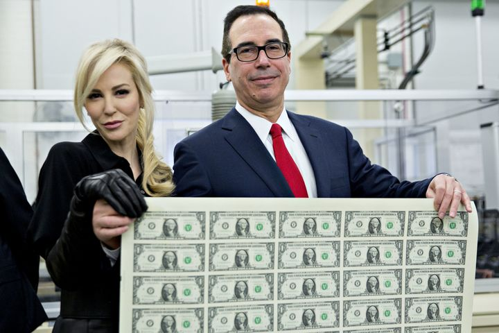 U.S. Treasury Secretary Steve Mnuchin poses with his wife, Louise Linton, while holding an uncut sheet of $1 dollar notes bea