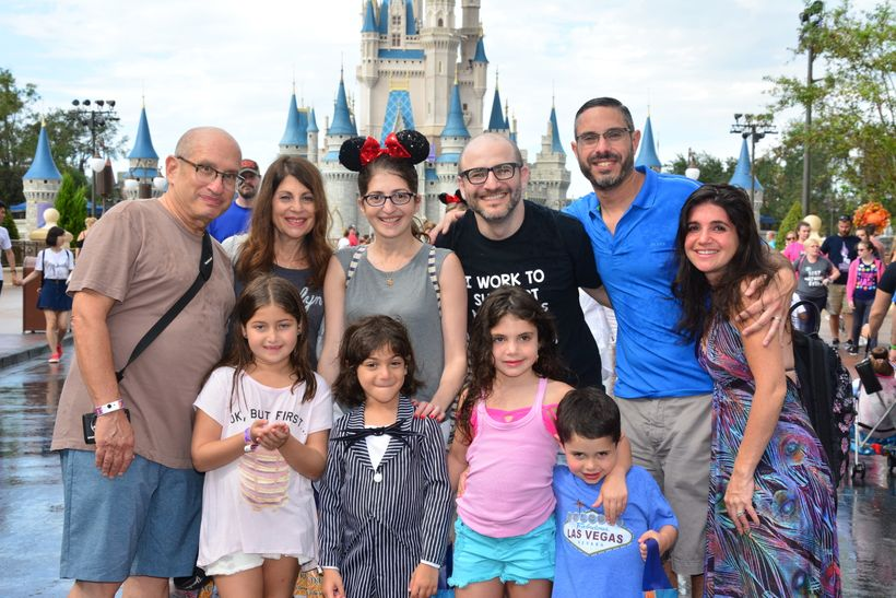 Three generations on a Disney World vacation, ages 4 to 68. Family photo in front of Cinderella's Castle at the Magic Kingdom