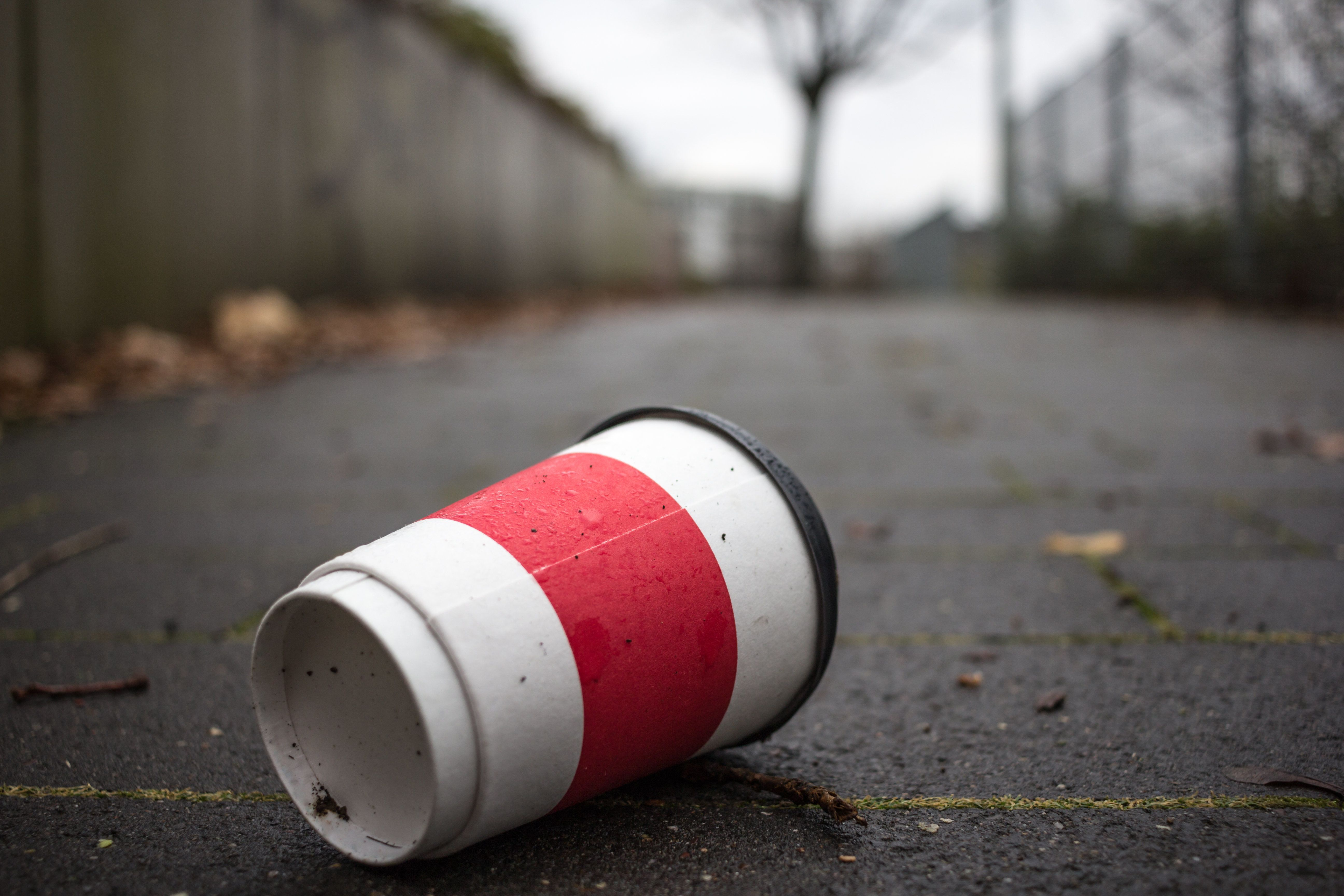 Used Coffee mug at sidwalk as symbol for pollution