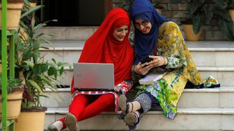 A student works on her computer sitting on stairs at Shaheed Benazir Bhutto Women's University in Peshawar, Pakistan October 19, 2017  REUTERS/ Fayaz  Aziz