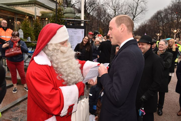 The Duke of Cambridge hands Prince George's Christmas wish list to Father Christmas at a market in Helsinki, Finland.