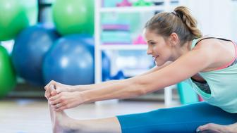 Attractive mid adult woman smiles as she touches her toes to stretch her leg at the gym.  She is on the floor using an exercise mat.