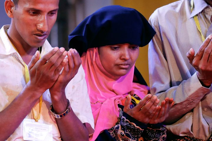 Tears run down the face of a woman as she and others pray during their meeting with Pope Francis in Dhaka, Banglade