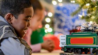 A brother and sister are playing with a toy train on Christmas morning.