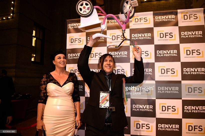 Novick holding up his most prized possession at the Denver Film Festival premiere of his film