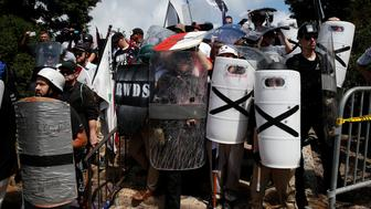 White nationalists shelter behind shields, displaying the Southern Nationalist flag, after clashing with counter protesters at a rally in Charlottesville, Virginia, U.S., August 12, 2017.   REUTERS/Joshua Roberts