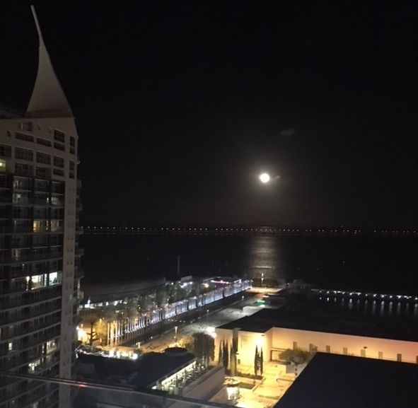 A full moon over the River Tagus, Park of Nations, and Altice Arena in Lisbon.