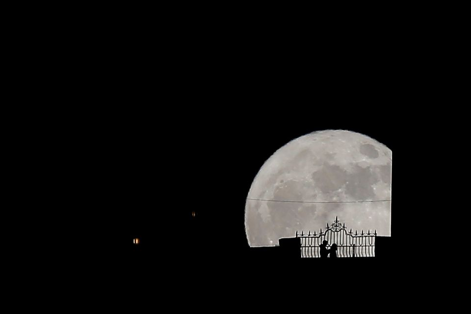 "People walk along the ""Puente Nuevo"" (New Bridge) as they are silhouetted against the supermoon during its rise in Ronda, sou"