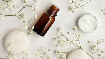 Bottle of essential oil, body care cream sample, stones, flowers.