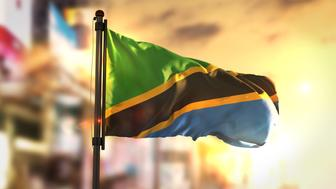 Tanzania Flag Against City Blurred Background At Sunrise Backlight