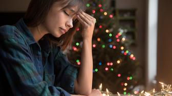 Mixed Race woman with headache near Christmas tree