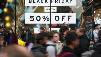 Shoppers pass a promotional sign for 'Black Friday' sales discounts on Oxford Street in London, on November 24, 2017. Black Friday is a sales offer originating from the US where retailers slash prices on the day after the Thanksgiving holiday. In the UK it is used as a marketing device to entice Christmas shoppers with the discounts at stores often lasting for a week. / AFP PHOTO / Daniel LEAL-OLIVAS        (Photo credit should read DANIEL LEAL-OLIVAS/AFP/Getty Images)