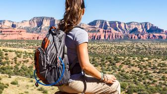 Woman takes a break from hiking and enjoys the landscape.