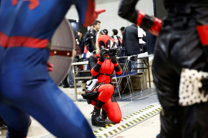 A woman in a Deadpool costume taking the picture of other cos players at Tokyo Comic-Con, Dec. 1.