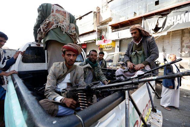 Houthi rebel fighters wait outside former President Ali Abdullah Saleh's residence in Sanaa on