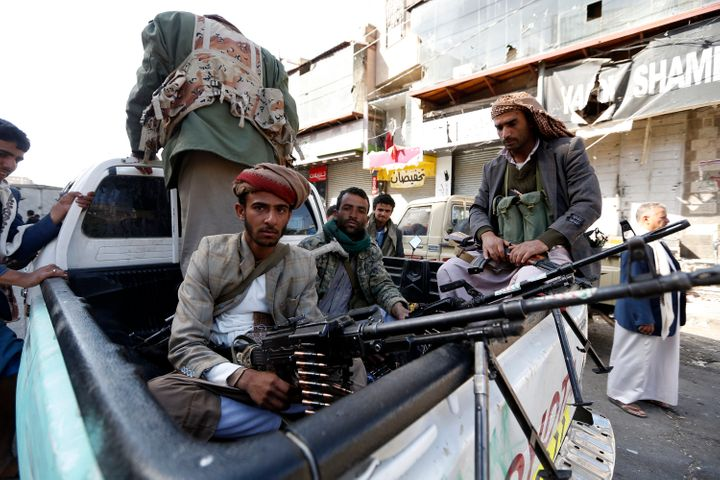 Houthi rebel fighters wait outside former President Ali Abdullah Saleh's residence in Sanaa on Monday.