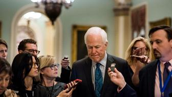 WASHINGTON, DC - Surrounded by questioning journalists just off the Senate floor, Senate Majority Whip John Cornyn  goes onto the floor during negotiations with Senators protesting a higher deficit result from the Senate tax bill's passage on Capitol Hill Thursday November 30, 2017. (Photo by Melina Mara/The Washington Post via Getty Images)