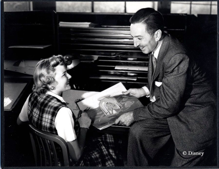"Ginni Mack, who worked as an inker, and Walt Disney review production artwork from ""Alice in Wonderland,"" circa 1950."