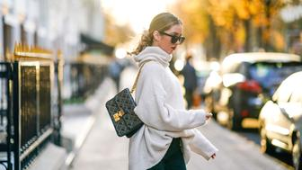 PARIS, FRANCE - NOVEMBER 19:  Rosa Crespo, fashion blogger, wears a Dior studded bag, Barney white boots, sunglasses, an Acne Studios white oversize sleeves sweater and a turtleneck, at avenue Montaigne, on November 19, 2017 in Paris, France.  (Photo by Edward Berthelot/Getty Images)